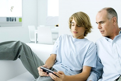 dad and teen watching phone video